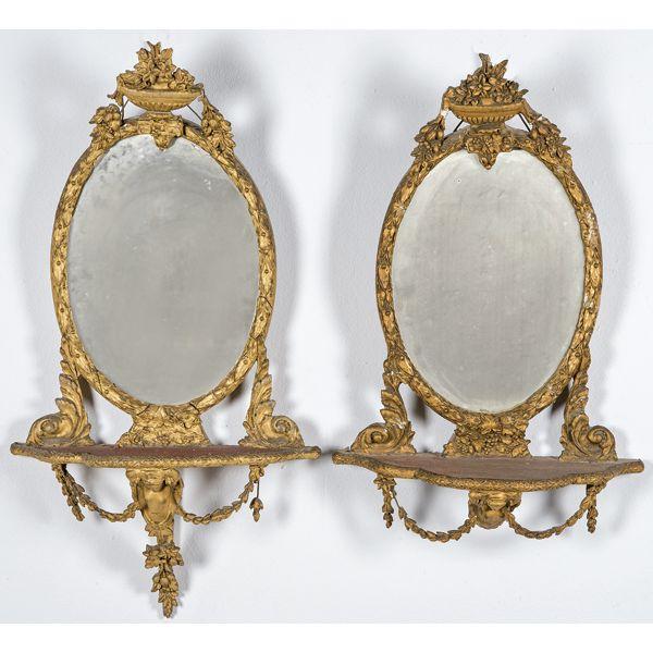 Pareja de espejos estilo ovales Jorge III con repisa en madera tallada, estucada y dorada.